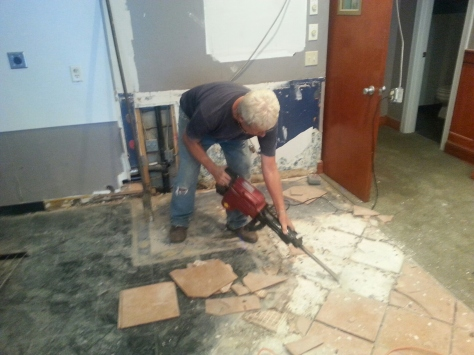 Dad removing some tile.  We scrapped the jackhammer as we found out that a simple spud bar easily removed the tiles whole - which we can then reuse.