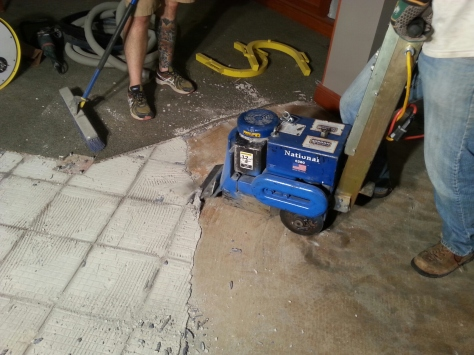 Another awesome machine, the 'Ripper Stripper'.  This beast is 300lbs and self propelled.  It has a vibrating blade to pull up tile and glue.  In this case we had thinset from an upper layer of ceramic tiles FIRMLY glued to the vinyl tile under it FIRMLY glued to the concrete floor under that.  Slow work even for this machine.