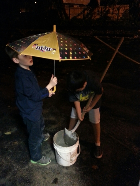 Trev and Dev mixing concrete in the drizzle.  The actually did all the mixing themselves and did a great job.