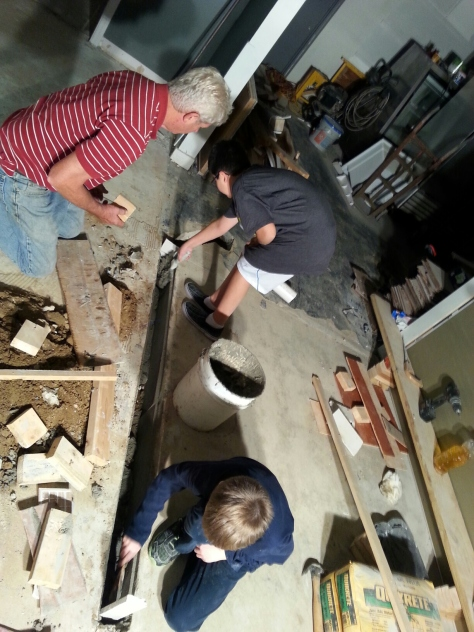 Dad and kids working on the floor of the trench drain.