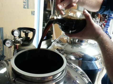 Pouring half a gallon of fresh espresso into the fermentor.