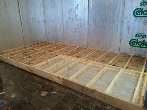 Filling in the 2x4's with rolled insulation after sealing the edges.