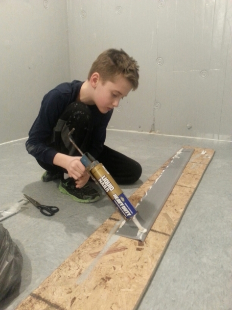 Devin applying glue to the cove base.  We are making this as waterproof as possible for spills or mopping.