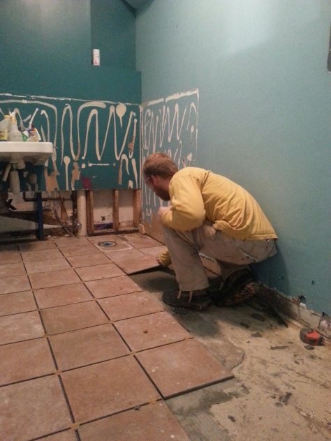 Me laying down tile in the Women's/ADA bath.  A lot easier than dealing with wood subfloors...I like a nice concrete pad!