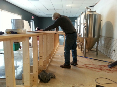 Dad working on finishing the first layer of the bar top while I paint.