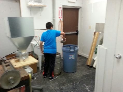 My son's first brewery job!  Emptying the grains out of the mashtun.