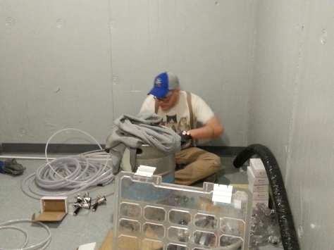 Alex sitting down on the job - hooking up keg line couplers.